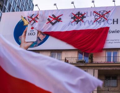 Flagi z wieloma symbolami wzdłuż trasy Marszu Niepodległości. Aktywiści...