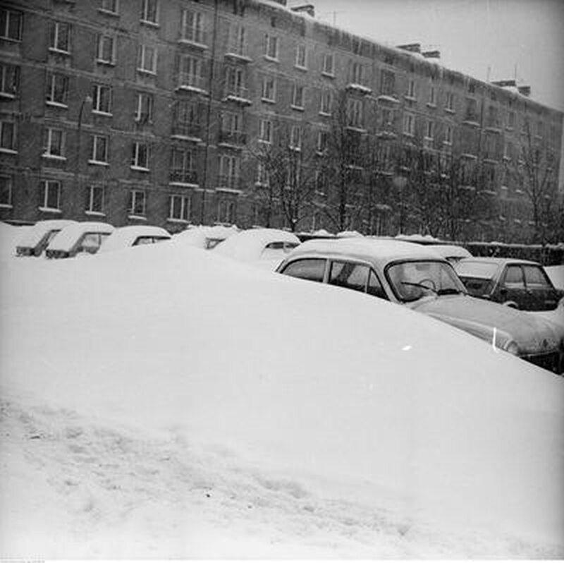 Zaspa śnieżna i zasypane samochody na parkingu. Na pierwszym planie samochód Syrena